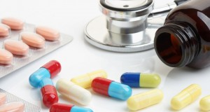 Close up of statin and beta-blocker pills and capsules with bottle and stethoscope.